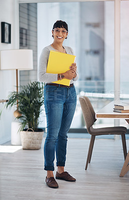 Buy stock photo Full length portrait of an attractive young businesswoman standing alone and holding files in her office
