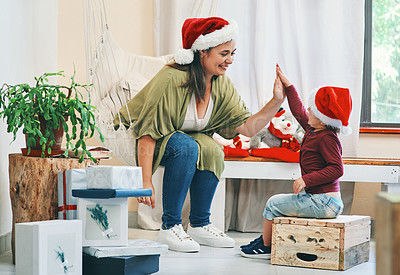Buy stock photo Shot of a young woman giving her adorable son a high five at Christmas