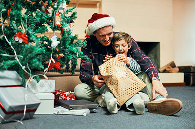 Buy stock photo Shot of an adorable little boy unwrapping Christmas presents with his father at home