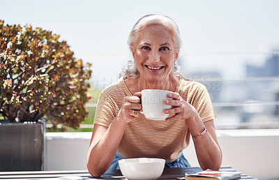 Buy stock photo Cropped portrait of an attractive senior woman enjoying her breakfast while sitting outside on the balcony at home