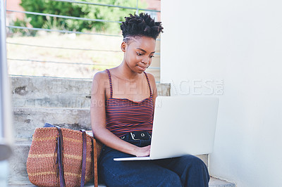 Buy stock photo Cropped shot of an attractive young female university student using a laptop while sitting outside her residence during the day