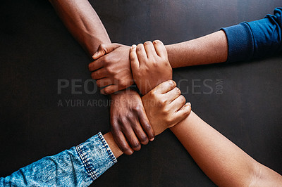 Buy stock photo High angle shot of a group of unrecognizable people holding hands tightly over a table