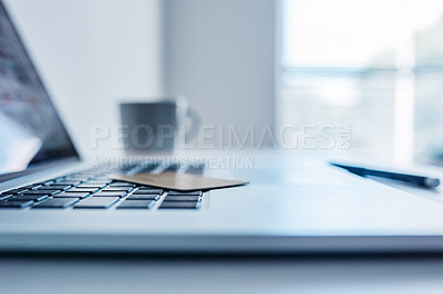 Buy stock photo Closeup of a credit card resting on top of a open laptop inside of a room during the day