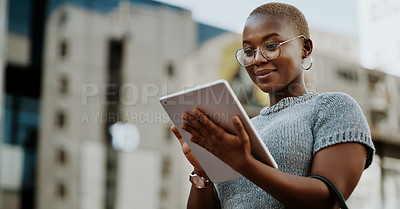 Buy stock photo Cropped shot of an attractive young businesswoman using her digital tablet while outdoors in the city