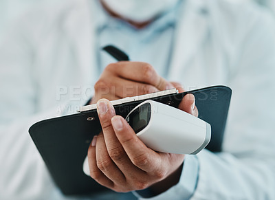 Buy stock photo Cropped shot of a doctor holding an infrared thermometer and writing notes during an outbreak
