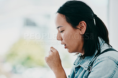 Buy stock photo Shot of a young woman coughing while waiting in a doctor's office