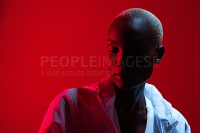 Buy stock photo Red filtered shot of a beautiful young woman posing in the studio
