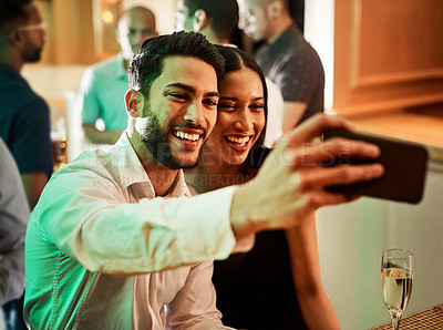 Buy stock photo Cropped shot of two cheerful young friends taking a self portrait together inside of a bar at night