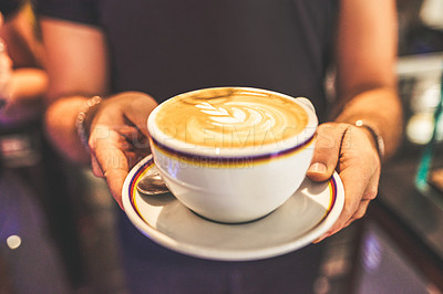 Buy stock photo Cropped short of an unrecognizable woman holding a cup of coffee to serve to a customer inside of a cafe during the day