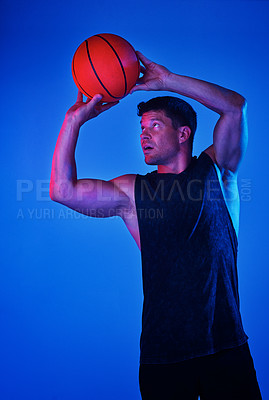 Buy stock photo Red filtered shot of a sportsman playing basketball in the studio
