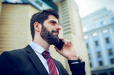 Buy stock photo Shot of a young businessman talking on a cellphone in the city