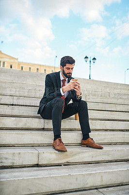 Buy stock photo Shot of a young businessman eating a pita sandwich while sitting on a staircase in the city