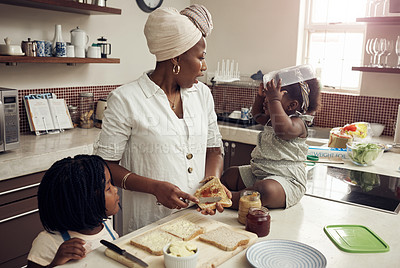 Buy stock photo Cropped shot of a young mother preparing a lunch meal for her two adorable young daughters at home