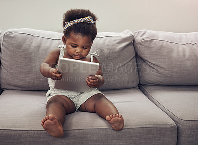 Buy stock photo Full length shot of an adorable baby girl using a digital tablet while sitting on a sofa at home