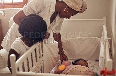 Buy stock photo Cropped shot of an adorable little girl and her mother watching her baby sister sleeping in her crib at home