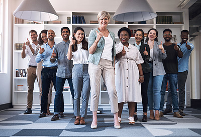 Buy stock photo Portrait of a diverse group of businesspeople showing thumbs up together in an office