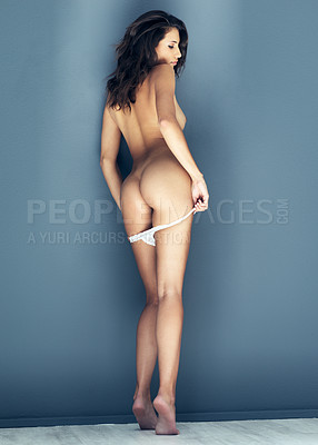 Buy stock photo Rearview shot of a sexy young woman posing nude against a grey background