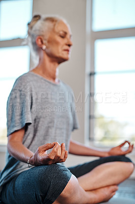 Buy stock photo Shot of a cheerful mature woman practicing yoga while meditating inside of a studio during the day