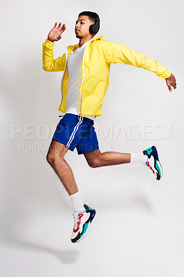 Buy stock photo Studio shot of a handsome young man listening to music while jumping in the air inside of a studio