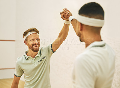 Buy stock photo Shot of two young men giving each other a high five before playing a game of squash