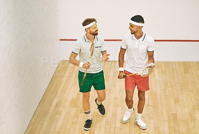Buy stock photo Shot of two young men chatting while playing a game of squash at an indoor court