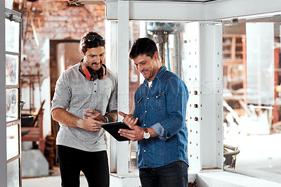 Buy stock photo Cropped shot of two young businessmen using a digital tablet while working together in an office inside their workshop