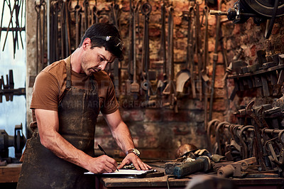 Buy stock photo Cropped shot of a handsome young craftsman filling out paperwork while working inside a metal workshop
