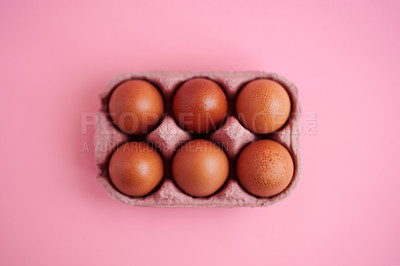Buy stock photo Studio shot of six chicken eggs in a carton against a grey background