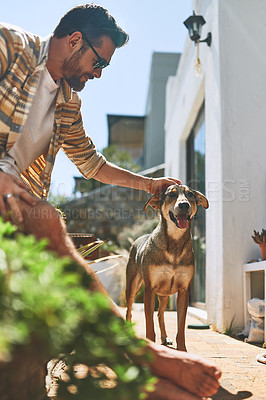 Buy stock photo Cropped shot of a cheerful young man petting his dog outside of his home during the day
