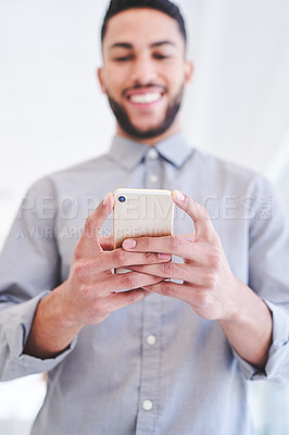 Buy stock photo Closeup shot of a young businessman using a cellphone in an office