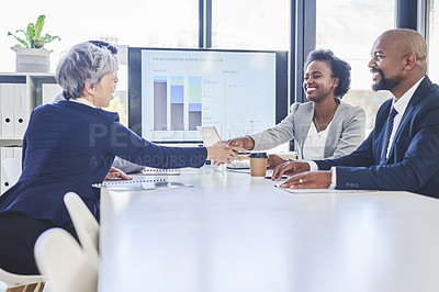 Buy stock photo Shot of two businesswomen shaking hands together during their meeting inside a boardroom