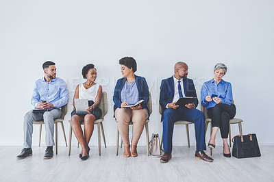 Buy stock photo Full length shot of a group pf businesspeople sitting down in line against a white background