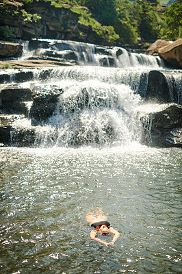 Buy stock photo Full length shot of an unrecognizable woman swimming in a stream alone during a day outdoors