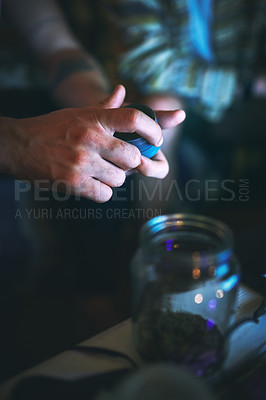 Buy stock photo Cropped shot of an unrecognizable man opening a tin of cannabis while sitting with his friend at home