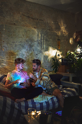 Buy stock photo Full length shot of two handsome young men using a smartphone together while sitting indoors at home
