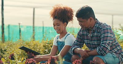 Buy stock photo Cropped shot of two young farmers using a digital tablet while working together in a crop field