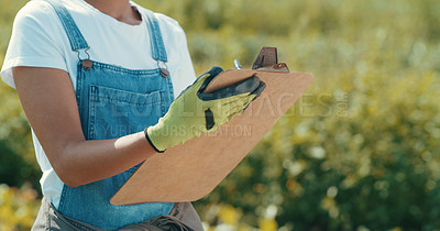 Buy stock photo Cropped shot of an unrecognizable female farmer writing on a clipboard while working in a crop field