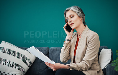 Buy stock photo Cropped shot of an attractive mature businesswoman sitting alone and using her cellphone while reading paperwork in her home office