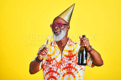 Buy stock photo Cropped shot of a funky and cheerful senior man celebrating and drinking champagne in studio against a yellow background