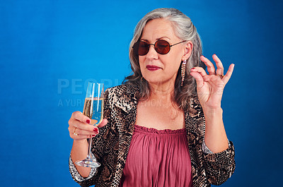 Buy stock photo Cropped shot of a funky and cheerful senior woman drinking a glass of champagne in studio