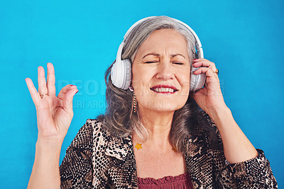 Buy stock photo Cropped shot of a funky and cheerful senior woman listening to music on her headphones against a blue background