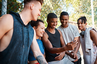 Buy stock photo Shot of a group of sporty young people looking at something on a cellphone while standing along a fence outdoors