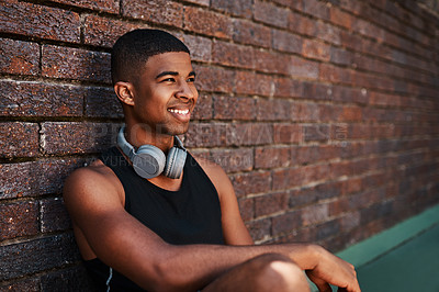Buy stock photo Shot of a sporty young man sitting against a wall outdoors