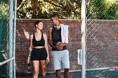 Buy stock photo Shot of two sporty young people chatting to each other while walking into a sports court