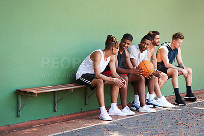 Buy stock photo Shot of a group of sporty young men taking a break after a game of basketball