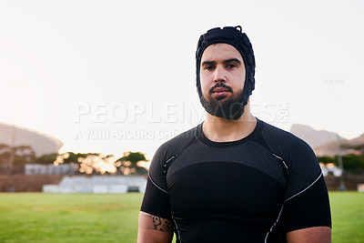 Buy stock photo Cropped portrait of a handsome young sportsman wearing headgear and standing alone during rugby practice during the day