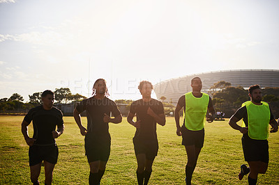 Buy stock photo Cropped shot of a diverse group of sportsmen warming up before playing rugby during the day