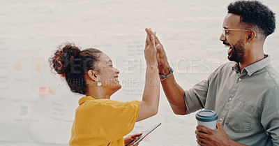 Buy stock photo Shot of two young businesspeople giving each other a high five in the office