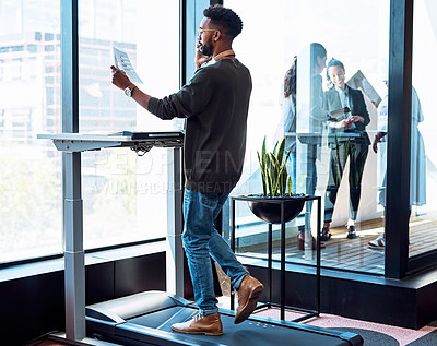 Buy stock photo Shot of a young businessman talking on a cellphone and going through paperwork while walking on a treadmill in an office