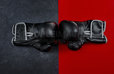 Buy stock photo High angle shot of a pair of boxing gloves placed together on top of a multi coloured background inside of a studio